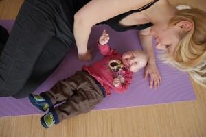 Lachendes Kind beim Mama Baby Yoga
